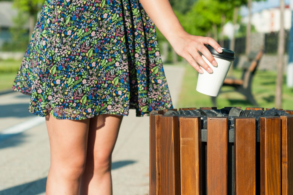 A woman putting her cup in the bin