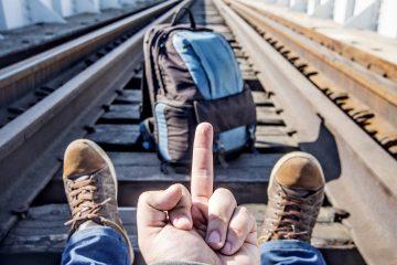 A man sitting on train tracks