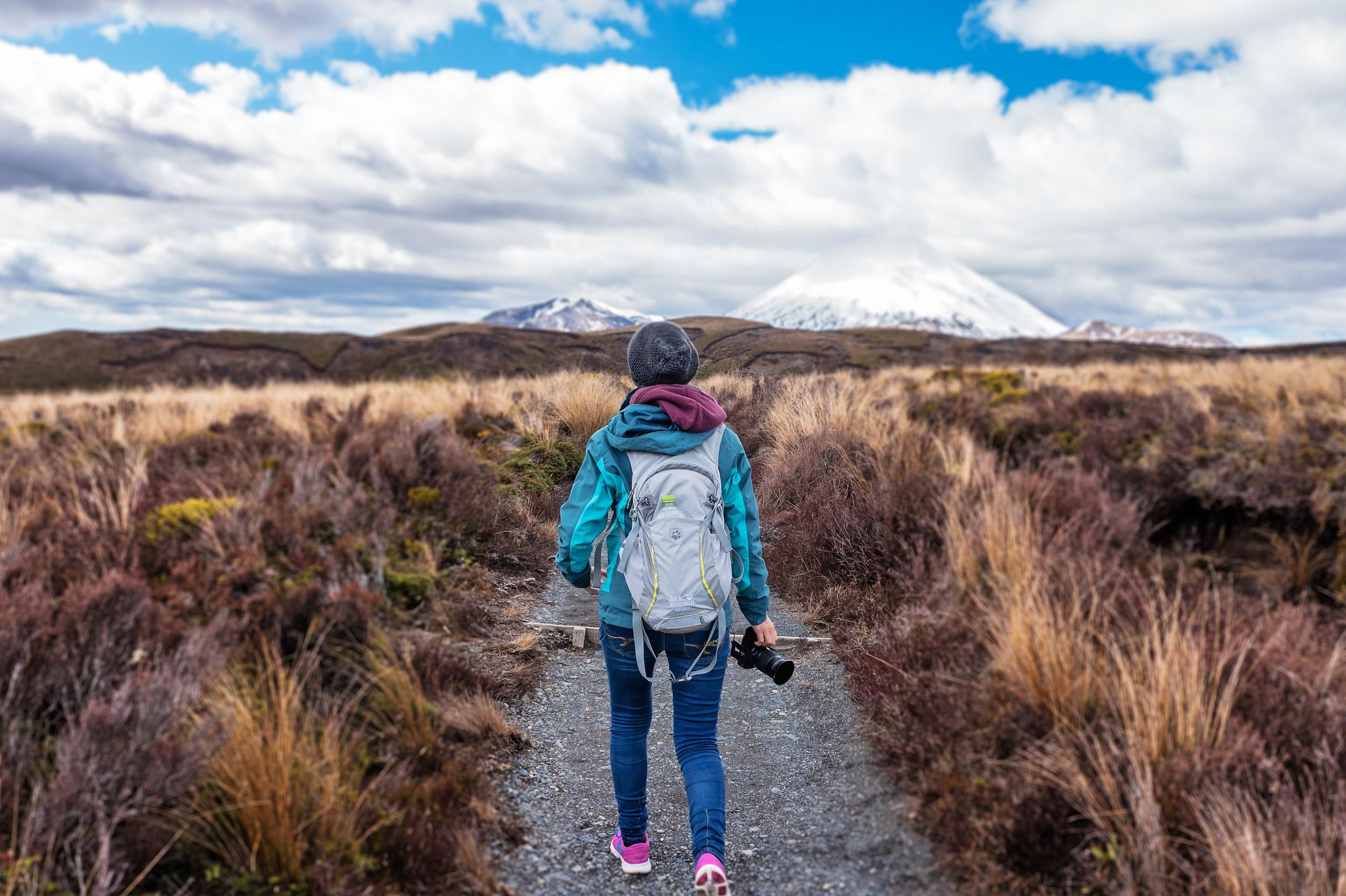 A woman hiking through fields