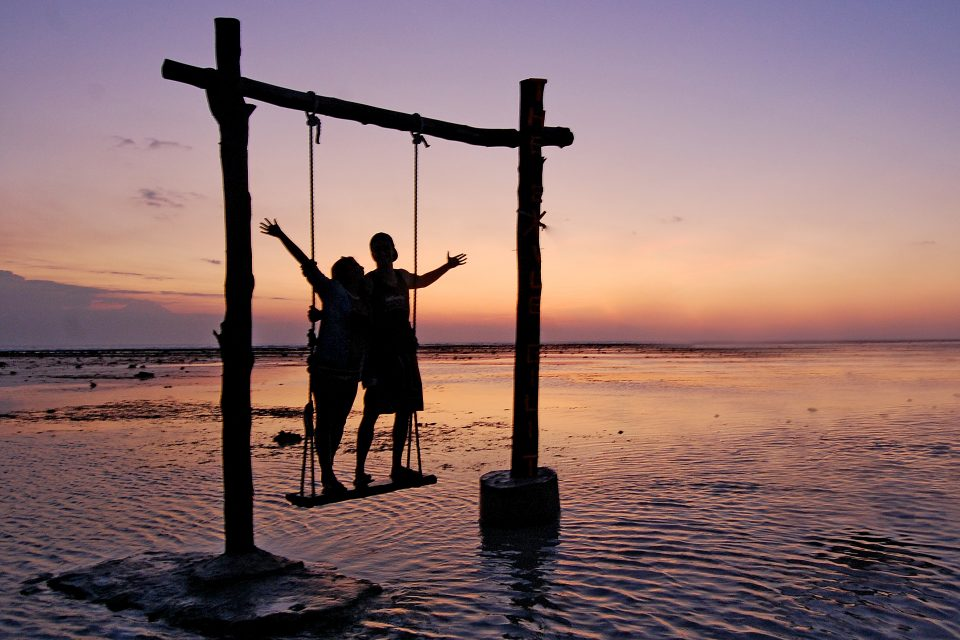 A couple's silhouette on a swing at sunset