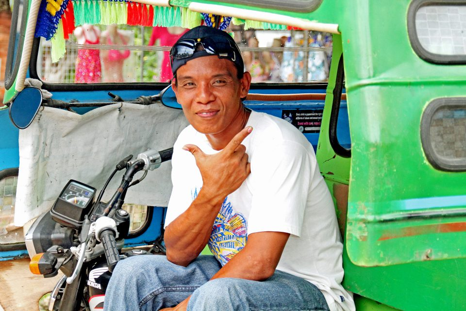 A local man sitting in his tuk tuk