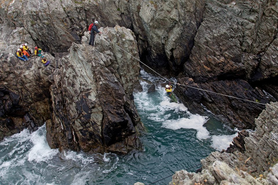 One man takes a zip line across rocks above water