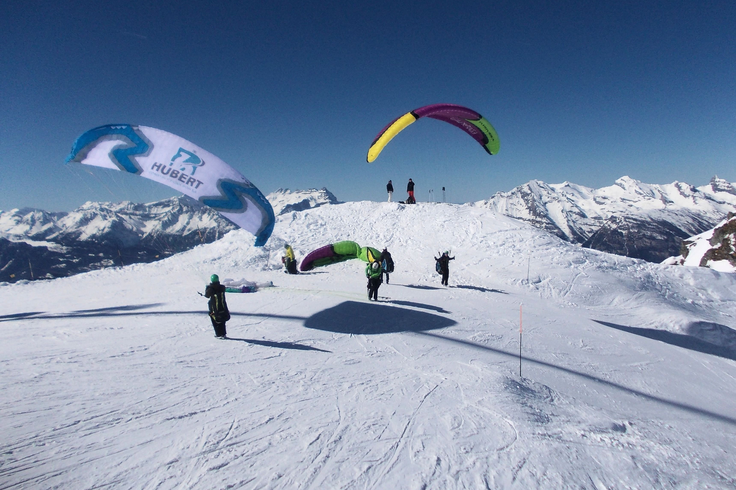 Group of paragliders land on snow