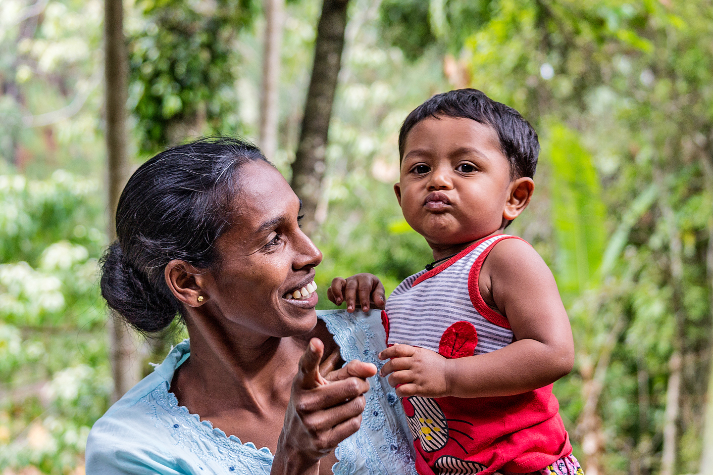 Portrait of young adult woman embracing little baby and pointing finger to the camera in Ella Sri Lanka