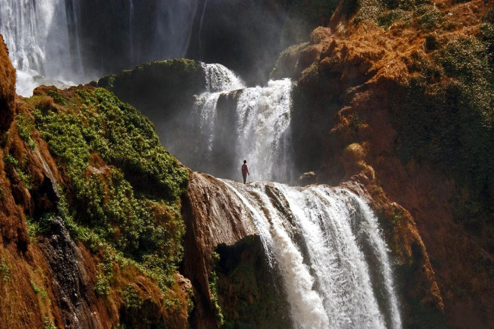 Man stands at the top of a waterfall