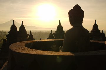 The sun rises in front of one of the many budda statues at Borobudur, Yogyakarta, Indonesia