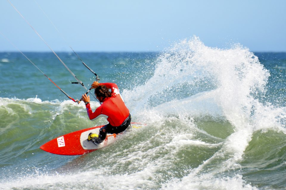 Guy in red wetsuit kitesurfing