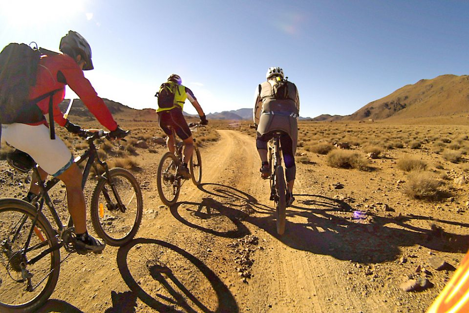 3 people ride mountain bikes through desert