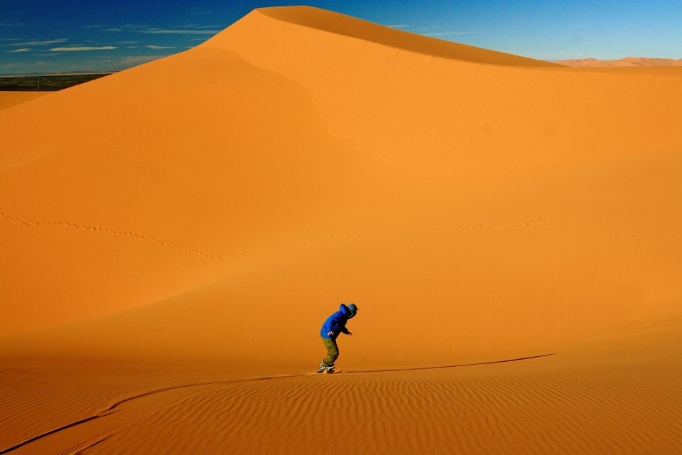 Sandboarder at bottom of sand dune