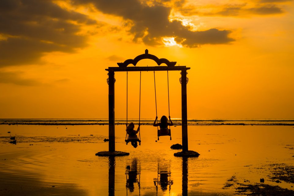 Two girls swing at sunset on Gili Islands, Indonesia