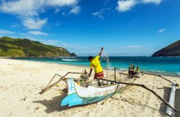 Fisherman in old boat at beach on Lombok, Indonesia
