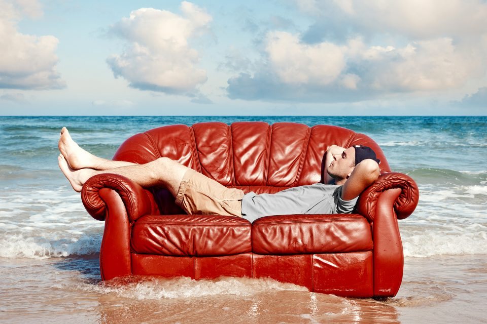 A man laying on a couch in the sea