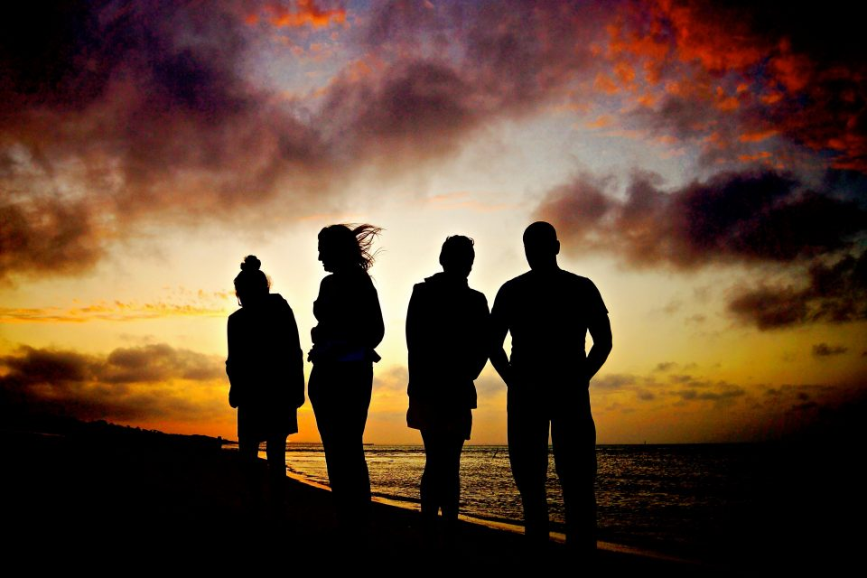 Silhouettes of a group of people at sunset