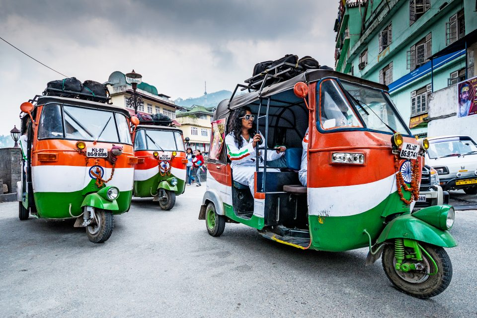 Three brightly coloured tuk tuks in India