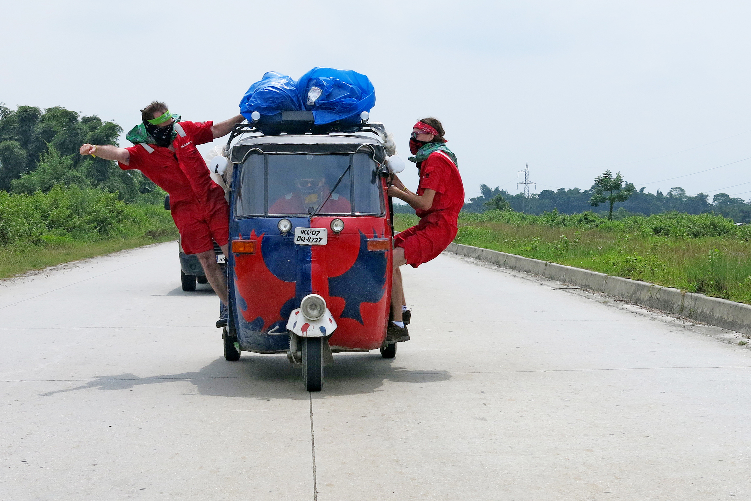 Two guys in masks hang out of a moving tuk tuk