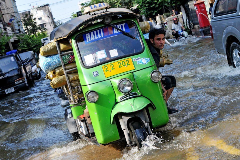 An auto rickshaw drives through rain