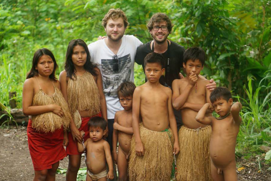 Two guys posing with an Amazonian tribe