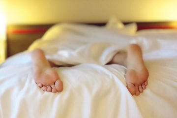 A person's feet sticking out the covers