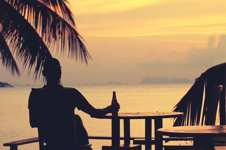 A man watching the sunset with a beer