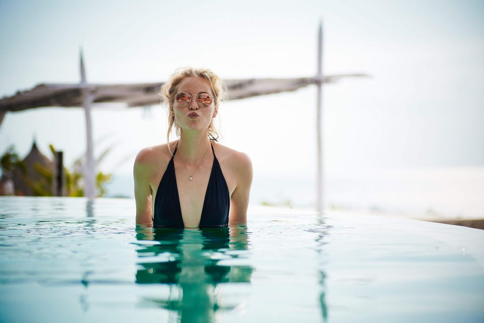A woman standing in an infinity pool