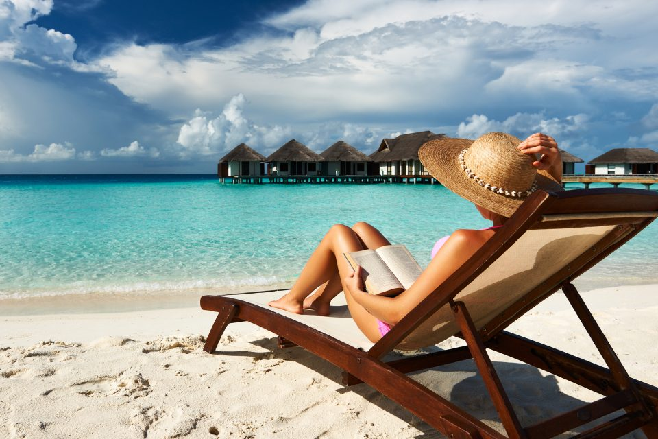 A woman sitting in a deckchair on the beach