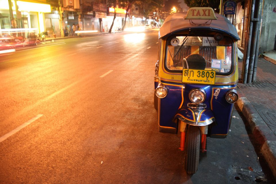 A tuk tuk parked on the side of the road
