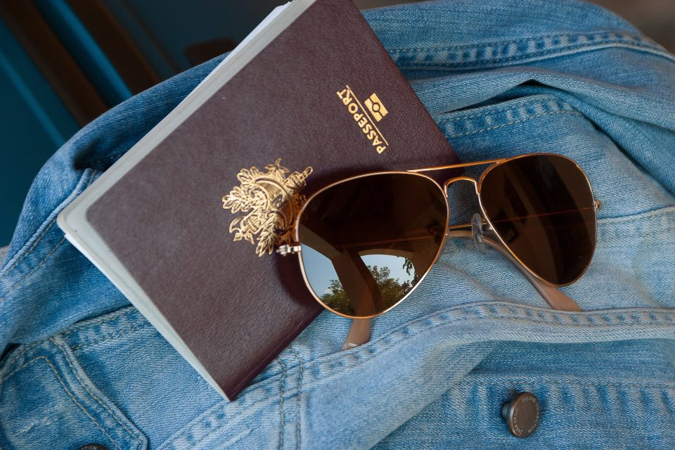 Passport and sunglasses on a denim jacket