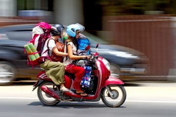 Female backpackers on a motorbike