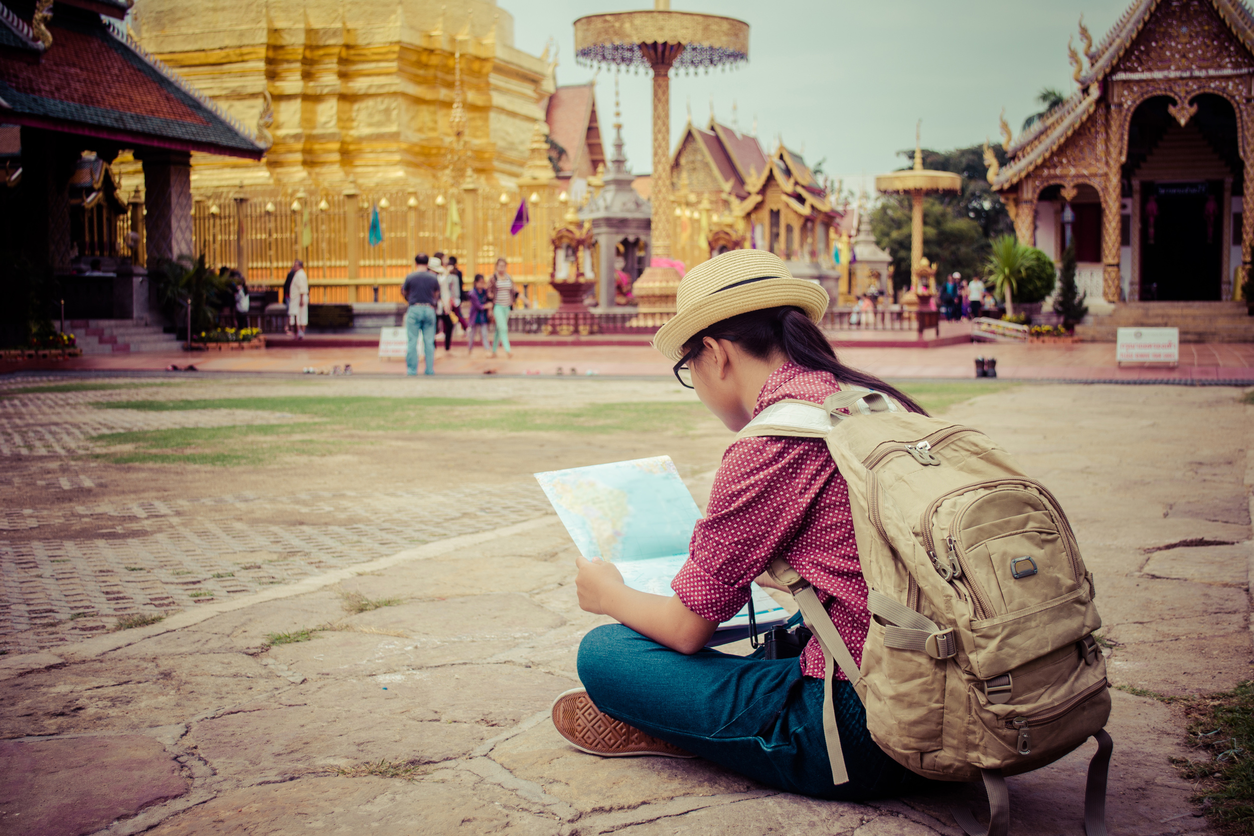 A woman sitting in front of a temple looking at a map