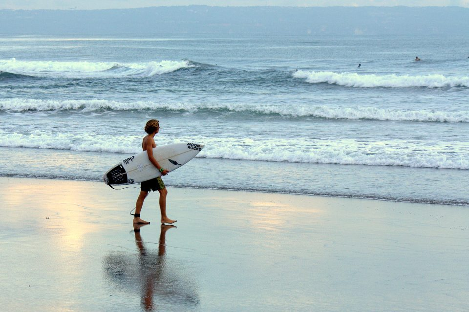 A man carrying a surfboard to the sea