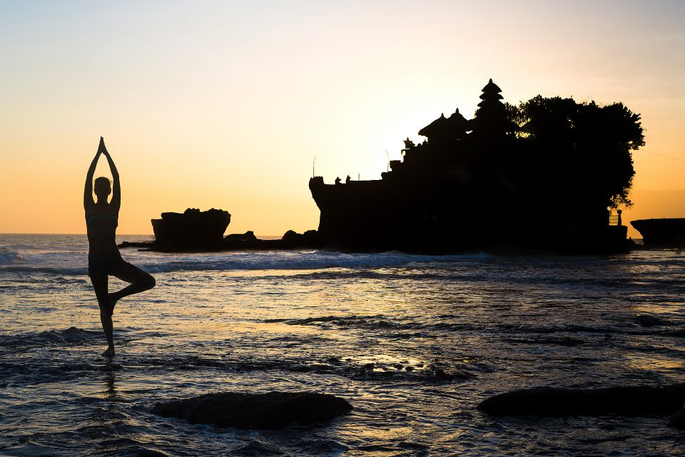 A woman doing yoga in the sea