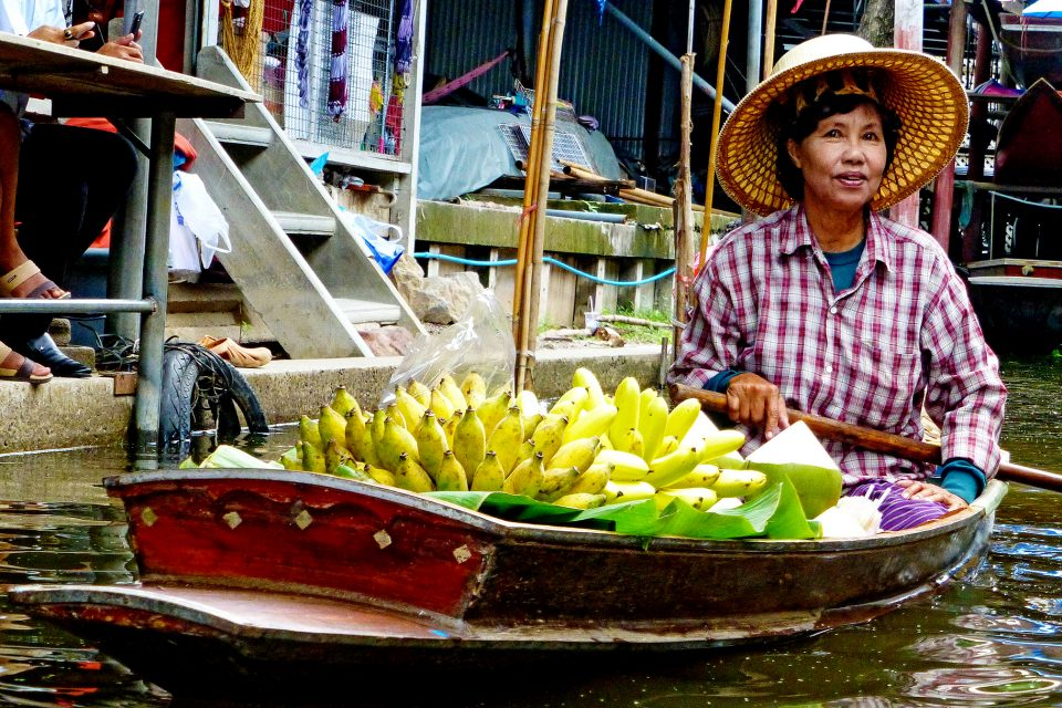 A local woman selling bananas from a canoe