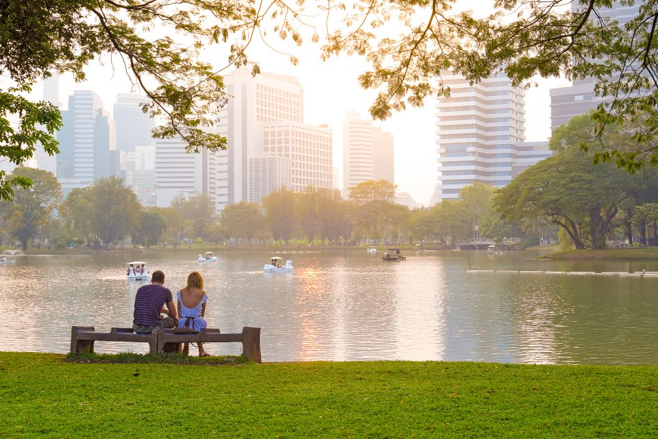 A couple sitting on a bench in lumpini park
