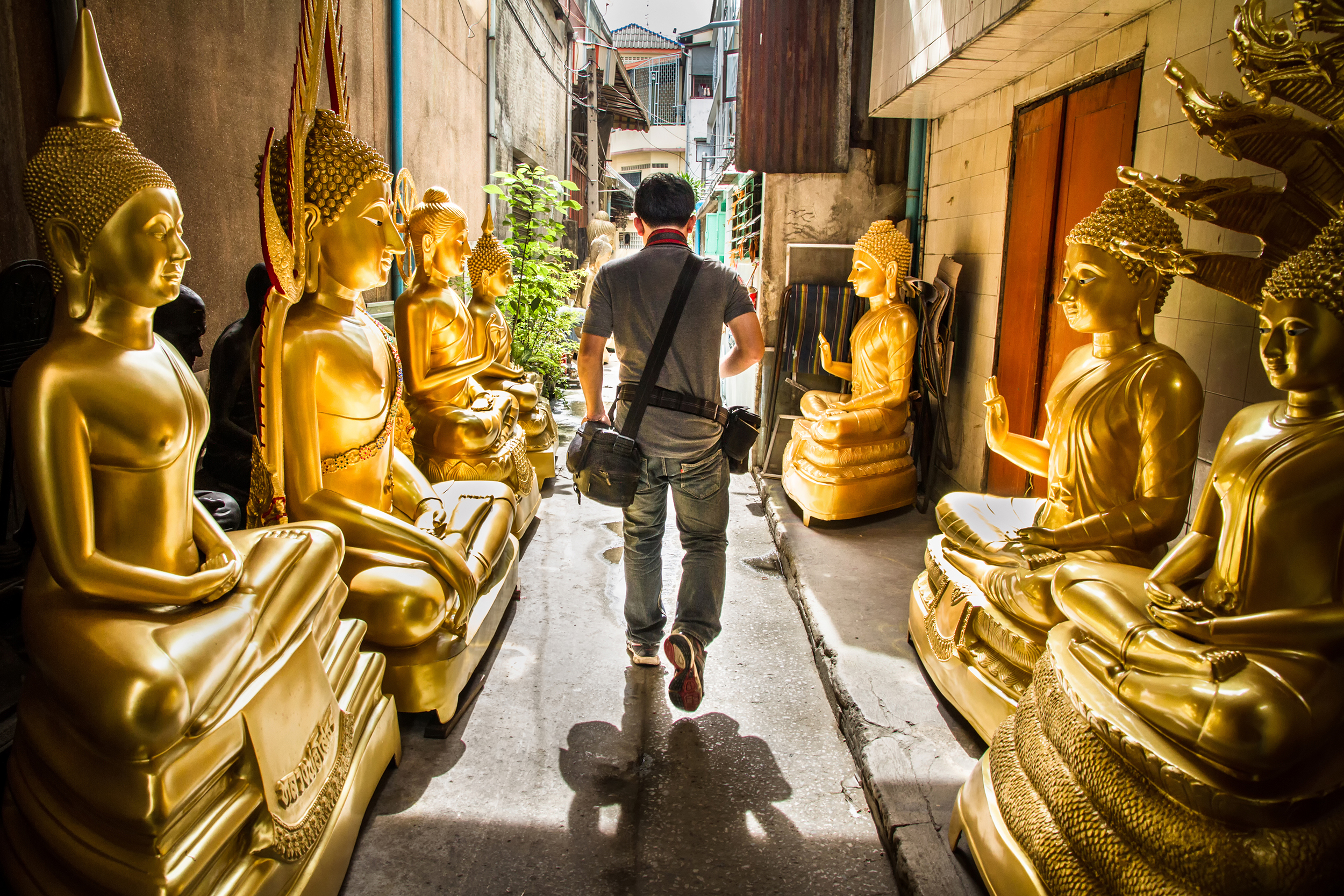 A man walking through the street lined with buddhas
