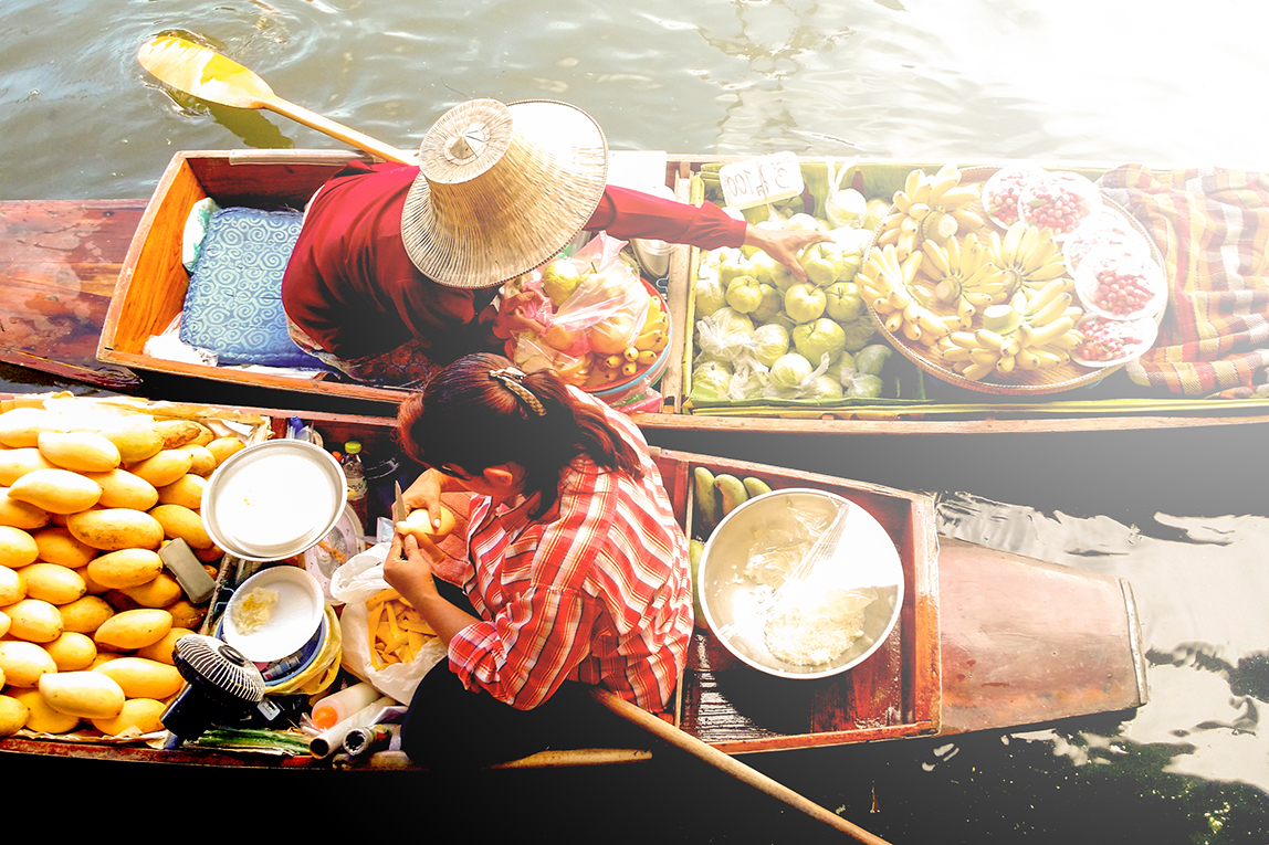 Two women selling fruit from canoes