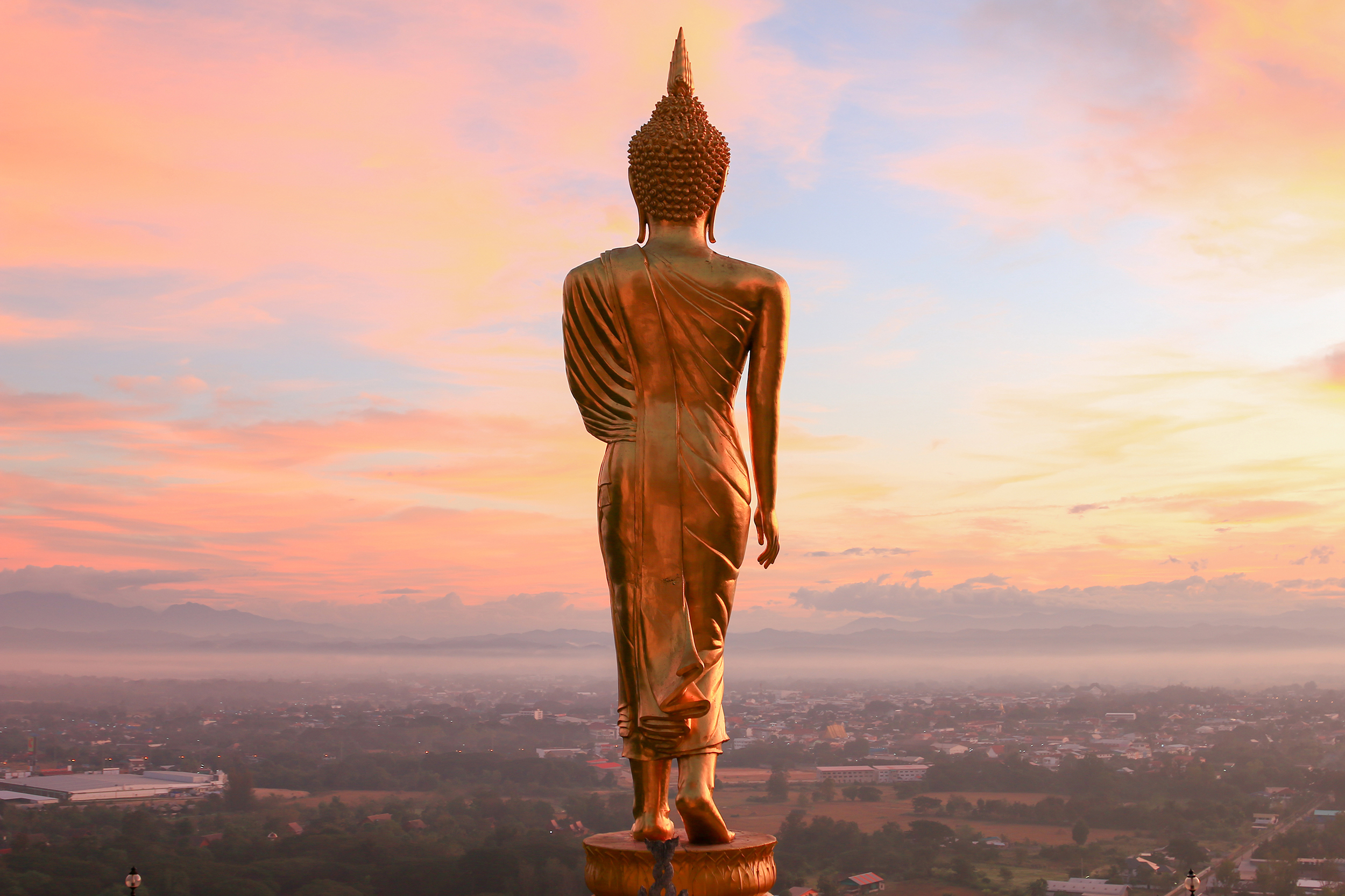 Golden buddha statue overlooking city
