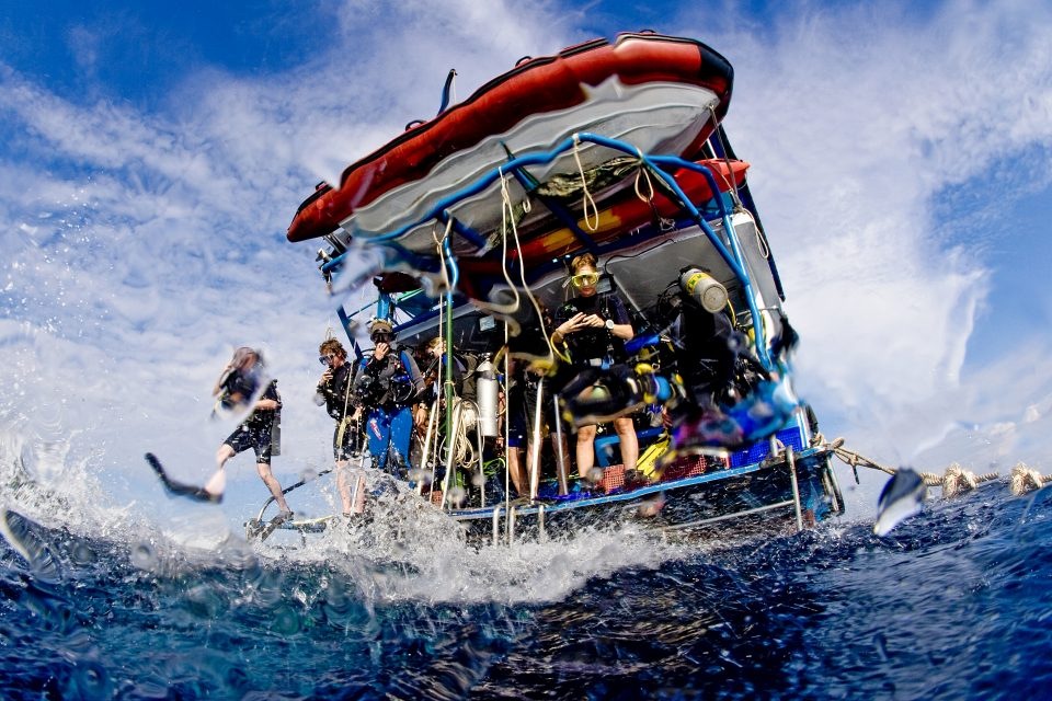 Group of divers preparing to dive of a boat, Thailand