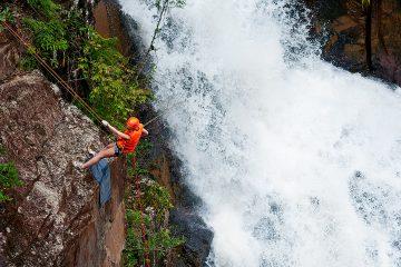A man abseiling down a waterfall