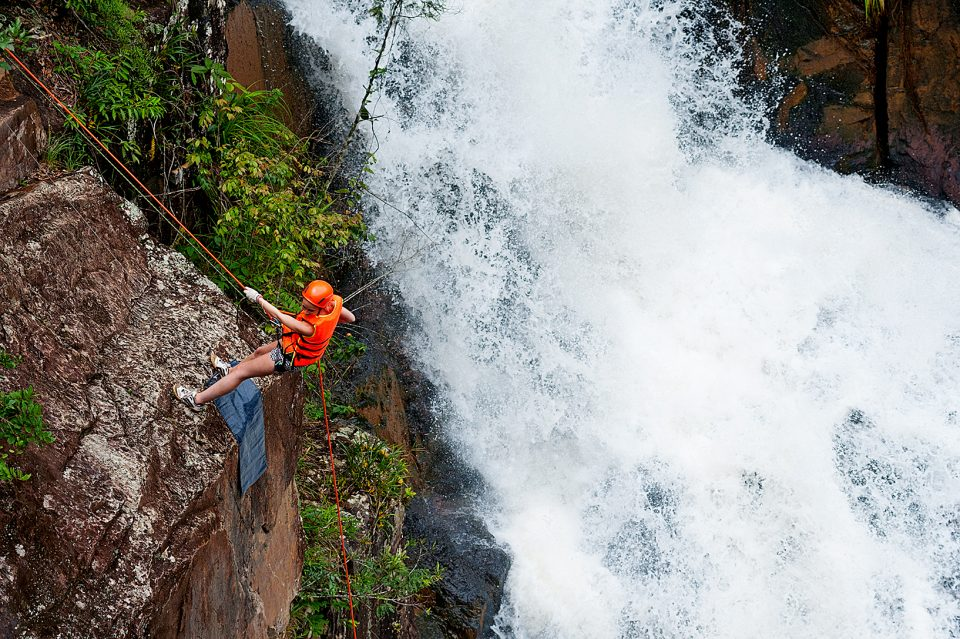 A man abseiling down a waterfall