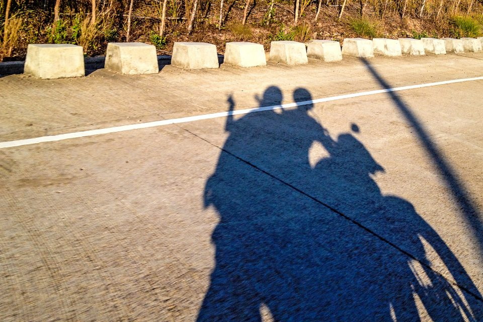 A shadow of a couple on a motorbike