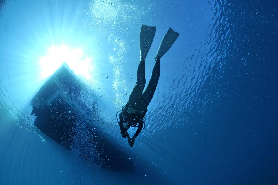 Upwards view of a diver surfacing at a boat