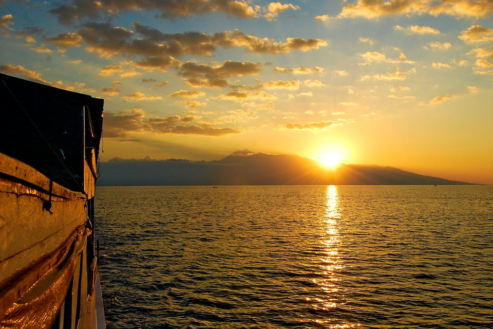 View of a sunset over a mountain from a boat