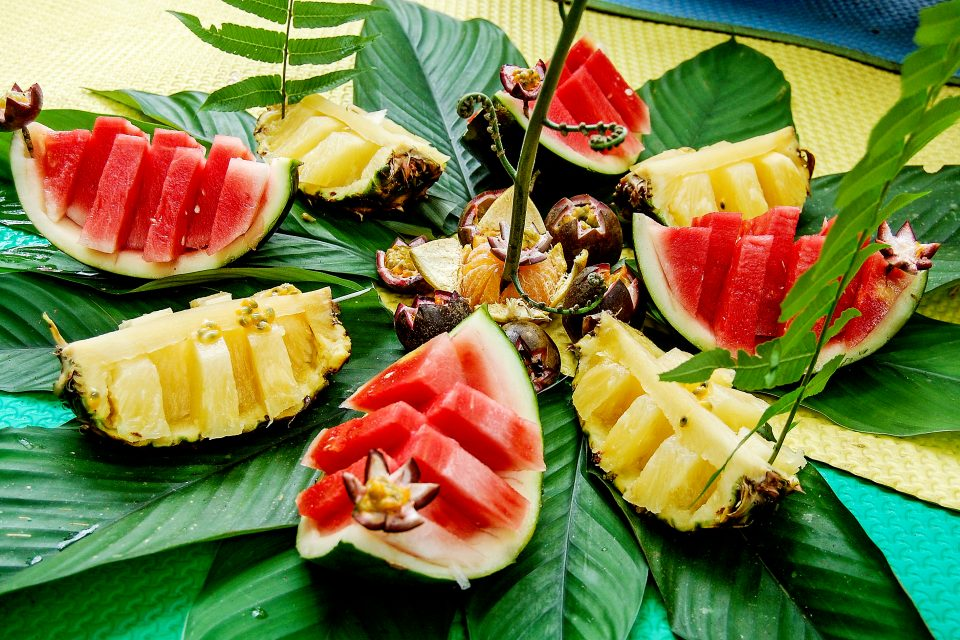 Watermelon and pineapple slices on banana leaves
