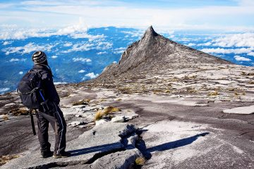 A man standing at the top of mount kinabalu