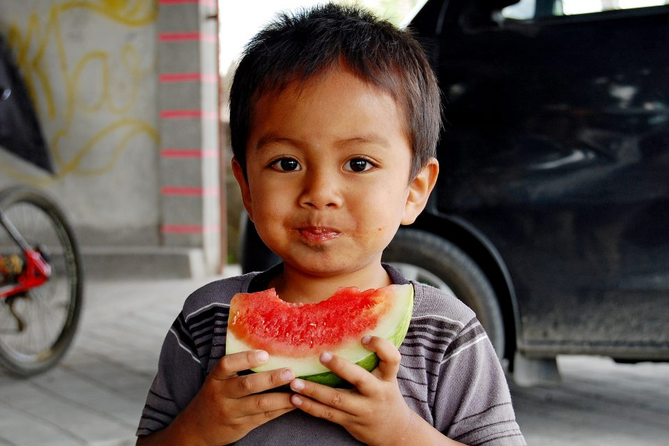 A young boy eating water melon