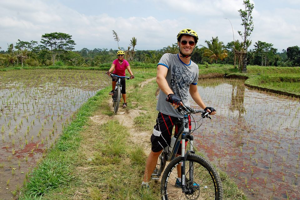A couple cycling through the rice fields