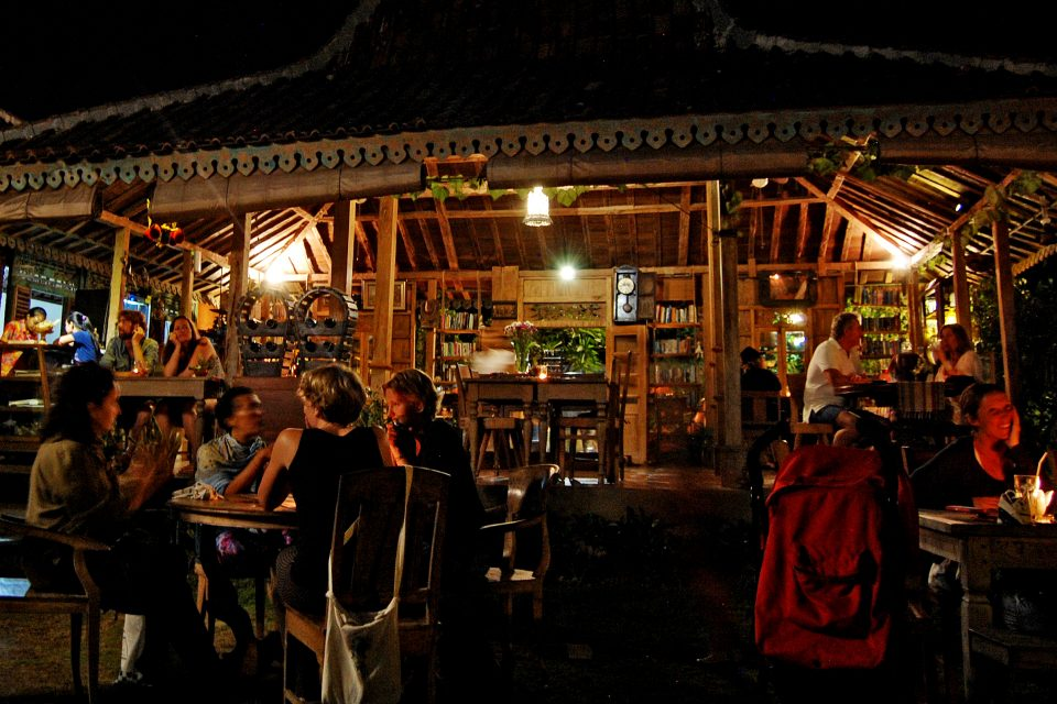 People sitting outside a wooden hut restaurant