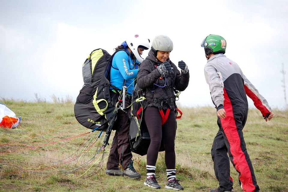 A woman getting geared up for paragliding