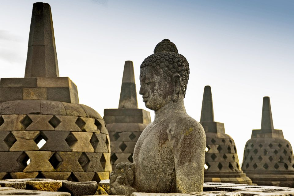 A stone buddha in front of temples