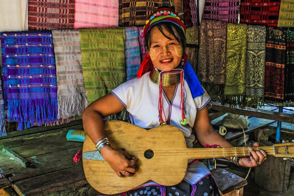 A tribe woman playing a guitar